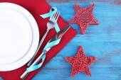 White plates, fork, knife and Christmas decoration on napkin on wooden background — Stock Photo