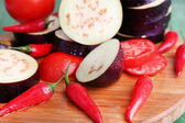 Chopped aubergines with tomatoes and chilly pepper on cutting board closeup — Stock Photo