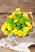Yellow and green flowers in basket on wooden background — Stock Photo
