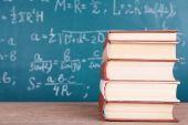 Boeken over houten tafel op blackboard achtergrond — Stockfoto