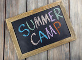 Text Summer camp written with chalk on chalkboard, and some chalk sticks of different colors — Stock Photo
