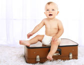 Cute baby boy sitting on suitcase in room — Stock Photo