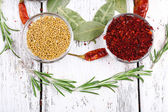 Spices with bay leaves, herbs and chilly pepper on wooden background — Stock Photo
