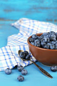 Tasty ripe blueberries in bowl, on wooden table — Stock Photo
