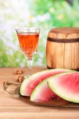 Composition of ripe watermelon, fruits, pink wine in glass and wooden barrel on  color wooden table, on bright background — Stock Photo