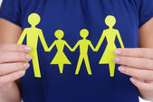 Woman hands holding paper family close up — Stock Photo