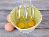 Cooking: whipping eggs with electric mixer in bowl on wooden table — Stock Photo