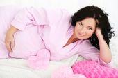 Jeune femme enceinte se trouvant sur le plaid avec des oreillers sur fond clair — Photo
