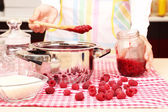 Woman cooking raspberry jam — Stock Photo