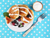 Tasty pancakes with fresh berries, cream and mint leaf on plate, on  color  background — Stock Photo