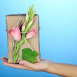 Female hand holding natural style handcrafted gift box with fresh flowers and rustic twine, on color background — Stock Photo #54044801