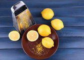 Lemons on plate and grater — Stock Photo