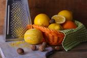 Lemons on napkin in basket, cutting board and grater on wooden background — Stock Photo