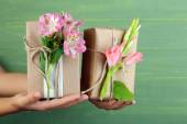 Female hand holding natural style handcrafted gift boxes with fresh flowers and rustic twine, on wooden background — Stock Photo