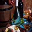 Supper consisting of Camembert and Brie cheese, honey, wine and grapes on napkin in basket and wine barrel on wooden table on brown background — Stock Photo #54056091