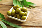 Green olives in bowl with leaves on table close-up — Stock Photo