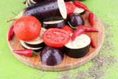 Chopped aubergines with tomatoes and chilly pepper on cutting board on wooden background — Stock Photo
