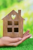 Woman hands holding small house on grass on bright background — Stock Photo