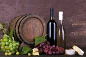 Wine in bottles and in goblet, Camembert and brie cheese, grapes and wooden barrel on wooden table on wooden background — Stock Photo