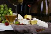 Supper consisting of Camembert and brie cheese, honey, wine and grapes on sackcloth on stand and wine barrel closeup — Stock Photo