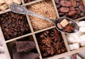 Wooden box with set of coffee and cocoa beans, sugar cubes, dark chocolate, cinnamon and anise, close-up — Stock Photo