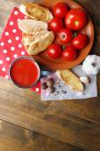 Homemade tomato juice in color mug, toasts and fresh tomatoes on wooden background — Stock Photo
