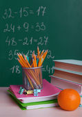 School supplies on table on board background — Stock Photo