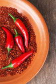 Red hot chili peppers  and milled pepper on plate, on wooden background — Stock Photo