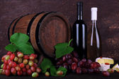 Wine in bottles, Camembert and brie cheese, grapes and wooden barrel on wooden table on wooden background — Stock Photo