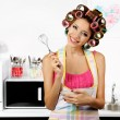Beautiful girl in hair curlers in kitchen — Stock Photo #54198343