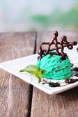 Lezzetli dondurma çikolatalı süslemeleri ve sos plaka, aydınlık arka plan üzerinde renkli ahşap masa — Stok fotoğraf