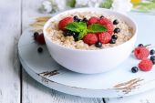 Tasty oatmeal with berries on table close-up — Stock Photo