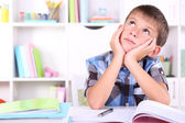 Schoolboy sitting at table in classroom — Stock Photo