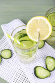Glass of cucumber cocktail on napkin on wooden background — Stock Photo