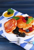 Tasty pancake with fresh berries and mint leaf on plate, on color wooden background — Stock Photo