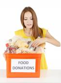 Girl volunteer with donation box with foodstuffs isolated on white — Stock Photo