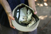 Homeless beggar money on his hat — Stock Photo