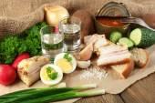 Bacon, legumes frescos, ovo cozido e pão no papel, copos de vodca em fundo de madeira. conceito de pequeno-almoço de aldeia. — Fotografia Stock