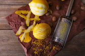 Lemons, nutmegs and grater on paper on wooden background — Stock Photo