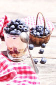 Natural yogurt with fresh blueberries on wooden table — Stock Photo