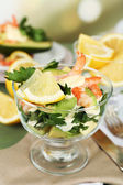 Tasty salads with shrimps and avocado in glass bowl and on plate, on wooden table, on bright background — Stock Photo