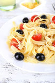 Spaghetti with tomatoes and olives and leaves — Stock Photo