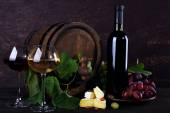 Wine in bottle and in goblets, Camembert cheese, grapes and wooden barrel — Stock Photo