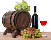 Wine in goblet and in bottle, grapes and barrel — Stock Photo