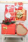 Christmas presents on ladder on brick wall background — Stock Photo