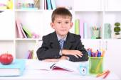 Schoolboy sitting at table in classroom — ストック写真