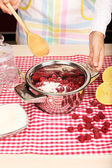 Woman cooking raspberry jam in kitchen — Stock Photo