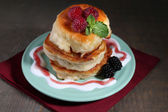 Tasty pancakes with fresh berries and mint leaf on plate, on wooden background — Stock Photo