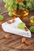 Brie cheese, honey in glass bowl, nuts and grapes on wooden background — Stock Photo