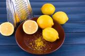 Lemons on plate and grater on dark blue wooden background — Stock Photo